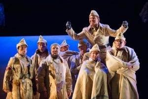 An opera production image showing a group of men in military attire. They are all dirty. Some are wrapped in blankets. They hold their leader aloft in celebration