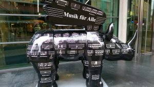 A sculpture of a winged rhinoceros. It is decorated with puns based on musical words and phrases.