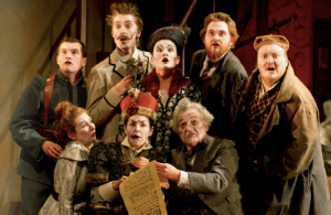 An opera production image. A group of characters look surprised as a will is read out