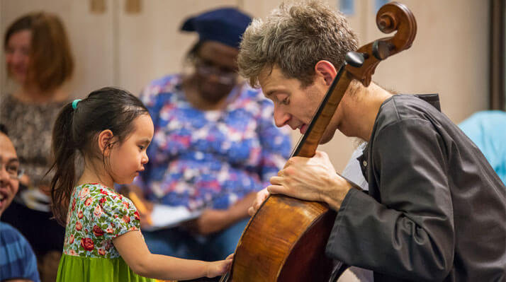 A cellist demonstrates his instrument to a small, excited child