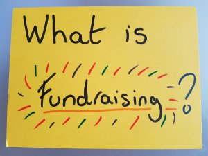 "A giant yellow post-it note, saying ""What is fundraising?"" in large letters"