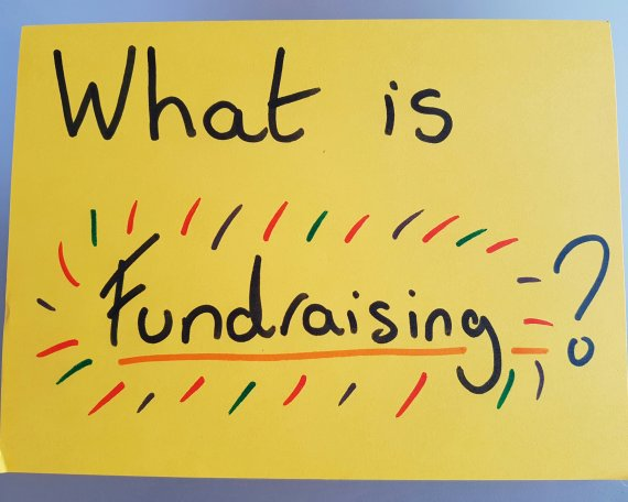 """A giant yellow post-it note, saying """"What is fundraising?"""" in large letters"""