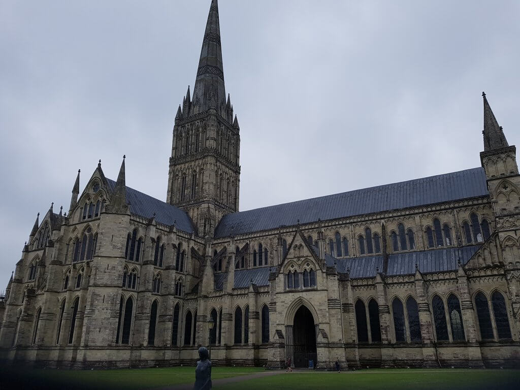 The outside of Salisbury Cathedral, showing the gigantic spire. The statue of a woman can be seen in front of the building