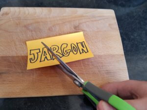 Scissors cut through a post-it with the word 'Jargon' written on it