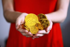 A woman in a red dress holds a handful of large gold coins