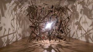Cornelia Parker's Cold Dark Matter: An Exploded View. A lightbulb hangs in the middle of the pieces of an exploded shed, casting shadows on the wall