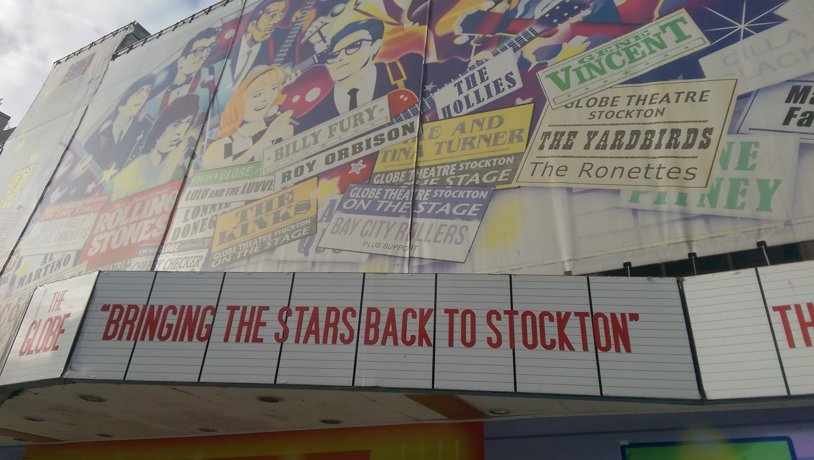 """The front of Stockton Globe covered in protective hoarding, showing posters for the many artists to perform there. A sign underneath says """"Bringing the stars back to Stockton"""""""
