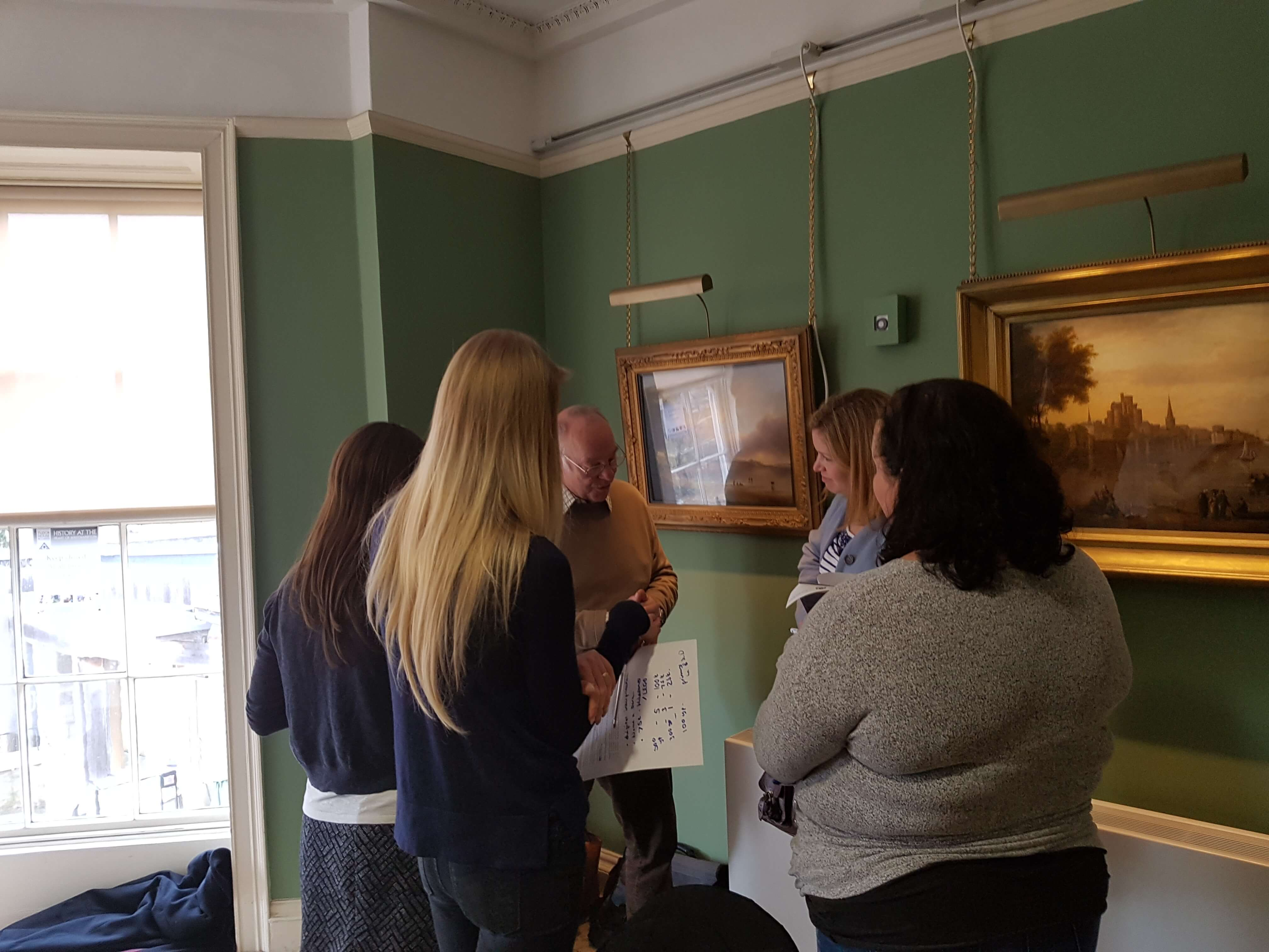 A group of museum fundraisers take part in a group activity during a training session