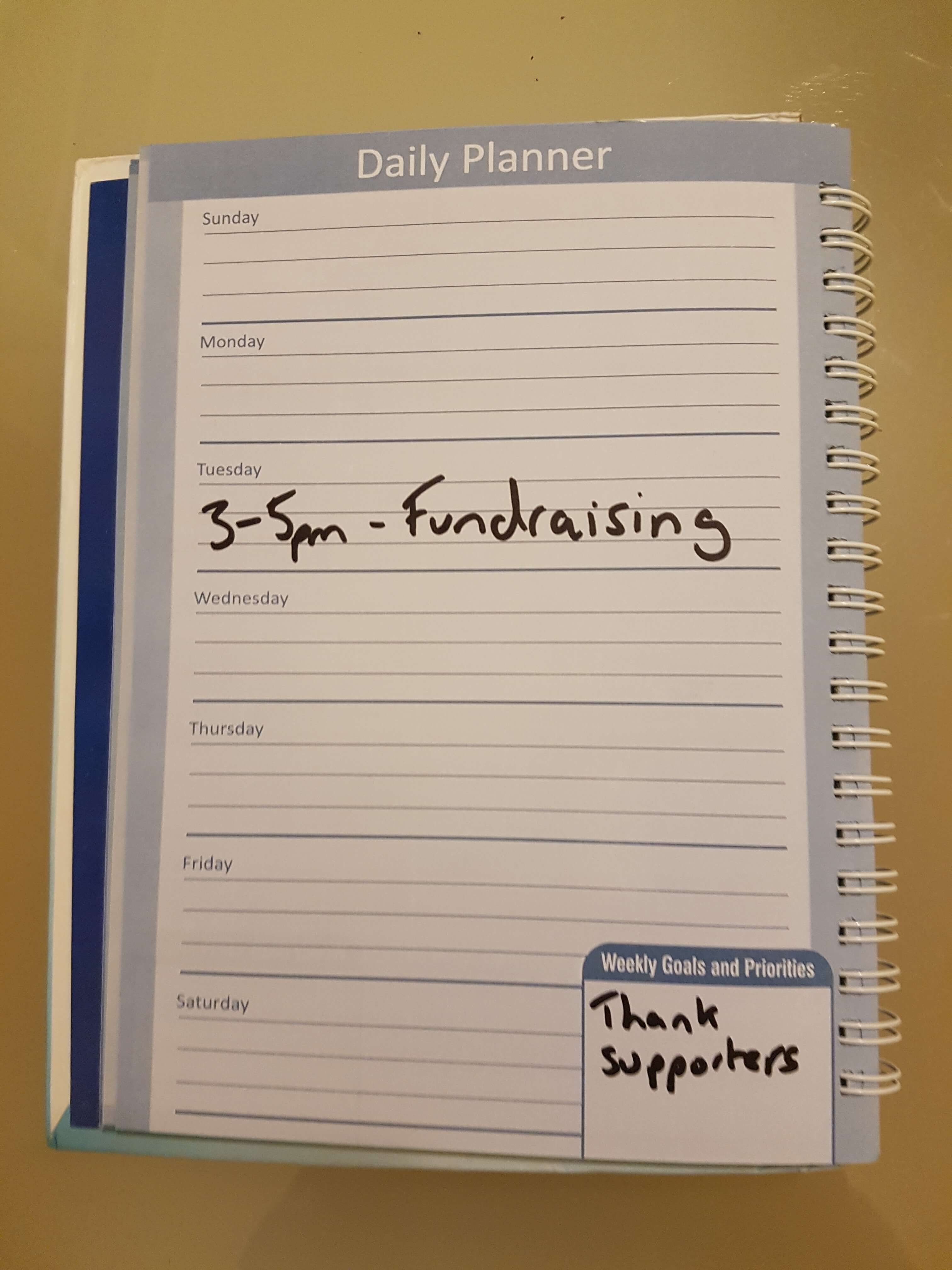 "A page of a Daily Planner. An entry between 3pm and 5pm says ""Fundraising"". In the weekly goals box it says ""Thank Supporters"""