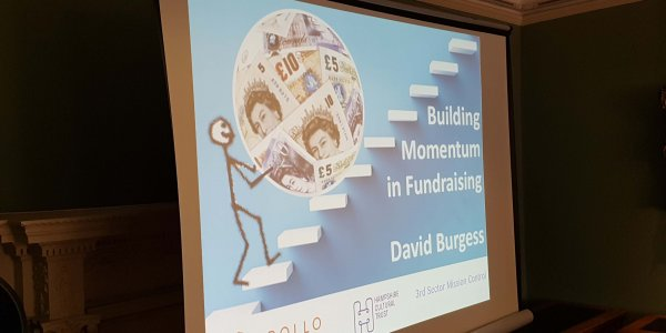 The title screen for a presentation called Building Momentum in Fundraising. It features a picture of a stick man pushing a ball of money up some stairs