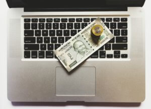 A laptop with money piled on the keyboard