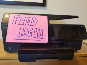A printer with a sign on saying 'Feed Me'
