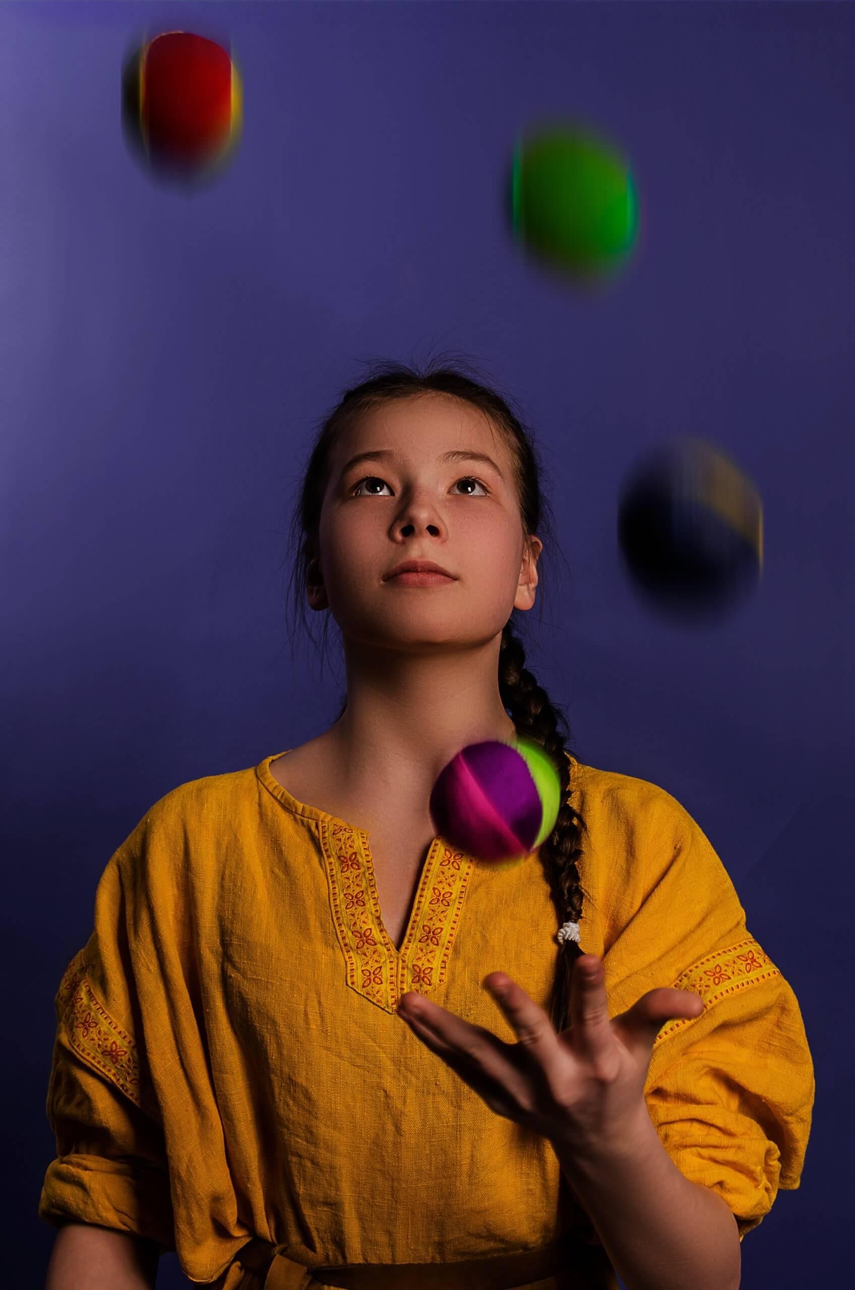 A woman juggles lots of different balls