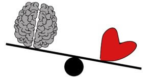 A brain and a heart on a set of scales. The heart outweighs the brain